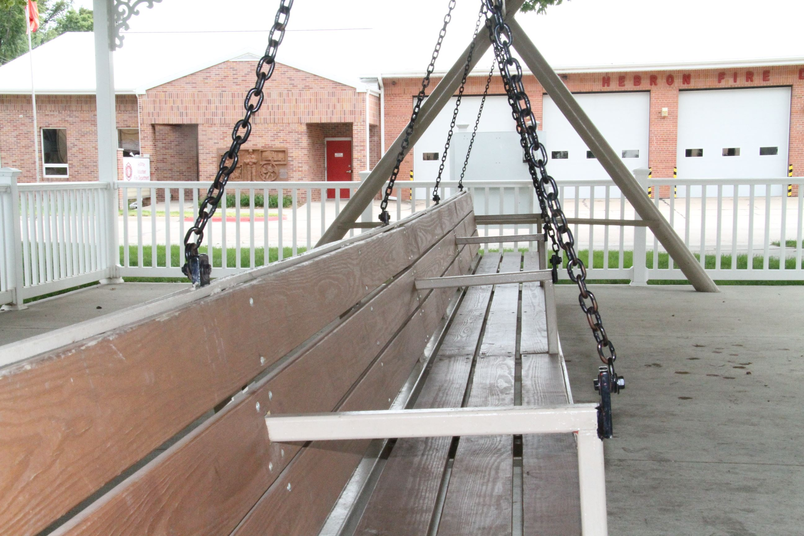 A long wooden porch swing hung by chains.